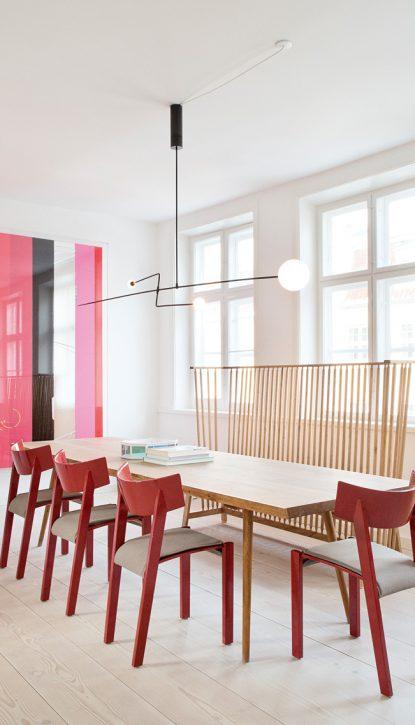 salle à manger avec un banc, Banc design Ilse Crawford (marque De La Espada) mis en ambiance de manière joyeuse par galerie danoise The Apartment. Luminaire mobile Chandelier de Michael Anastassiades, chaises vintage de Ralf Lindberg, Table de Kobenhavns Mobelsnedkeri.