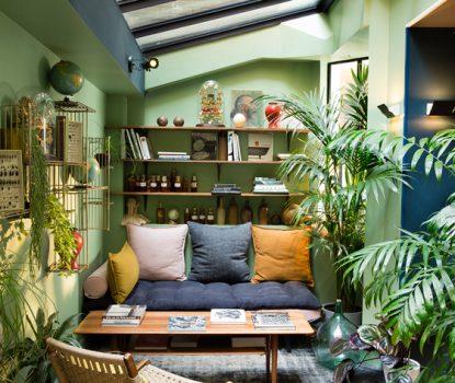 salon végétal.Dans cet espace où de la peinture verte recouvre les murs, des plantes de toutes les tailles ont été disséminées partout dans la pièce, notamment sur des étagères murales. Le puit de lumière contribue à relier le décor à son environnement extérieur.